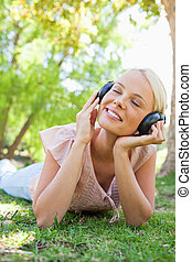 Smiling woman with headphones enjoying music on the lawn -...