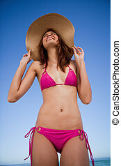 Low-angle view of a smiling teenager wearing a pink swimsuit...