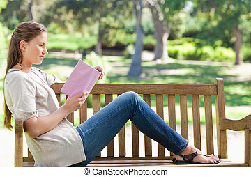 Side view of a woman reading a novel on a park bench - Side...