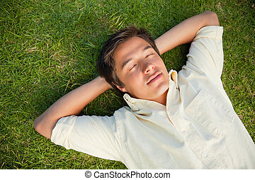 Man lying with his eyes closed and both hands behind his...