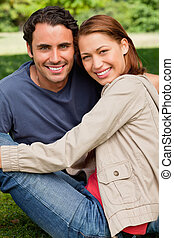 Two friends smiling and looking in front of them as they sit next to each other on the grass in a bright parkland