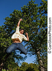 Man raising his arms and legs as he jumps in celebration -...