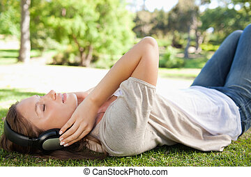 Woman lying on the lawn while enjoying music - Young woman...