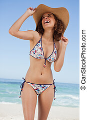 Young beautiful woman holding her hat while laughing in...