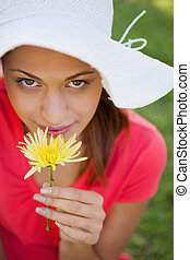 Woman wearing a white hat while smelling a flower while...