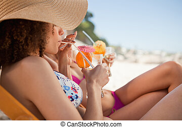 Side view of an attractive woman sipping her fruit cocktail accompanied by a friend