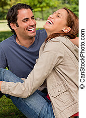 Two friends gleefully laughing as they are sitting next to each other on the ground in a shaded area of a park