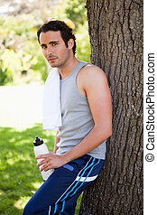 Man with a towel on his shoulder looking towards side while holding a water bottle and resting against the trunk of a tree