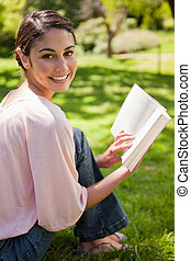 Woman looks to her side while reading a book in a park