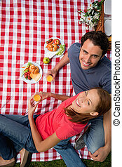 Elevated view of two smiling friends looking upwards while they hold glasses as they lie on a blanket with a picnic