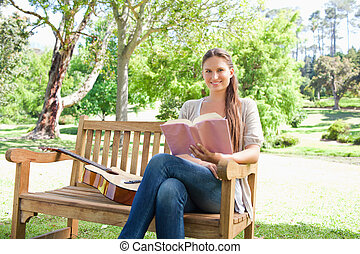 Smiling woman with a book and a guitar sitting on a bench