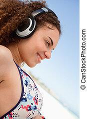 Beautiful young woman in bikini listening to music on the beach