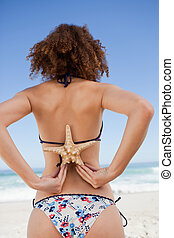 Young woman in swimsuit holding a starfish on her back -...