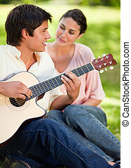 Man looking ahead and smiling as he is playing the guitar and being watched by his friend who is sitting next to him on the grass