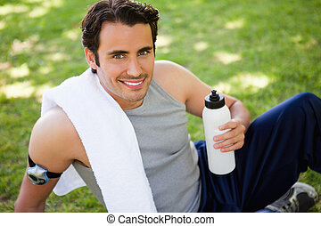 Man smiling with a white towel on his shoulder looking at the camera while holding a sports bottle