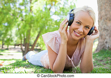 Smiling woman lying on the grass while listening to music