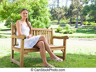 Woman with her legs crossed sitting on a park bench - Young...