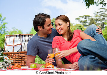 Two smiling friends looking into each others eyes while they hold glasses as they lie on a blanket with a view of the sky in the background