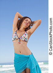 Young woman standing upright on the beach while showing her wellness