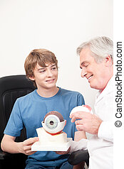 Optometrist and Patient - Optometrist showing medical eye...