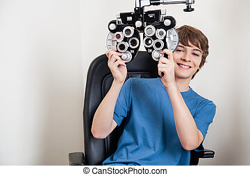 Eye Checkup With Phoropter - Teenager smiling while holding...