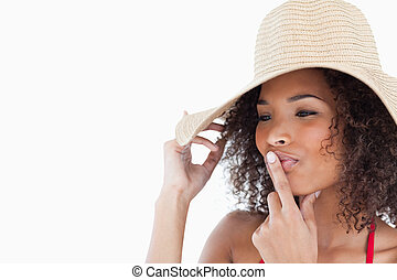 Young brunette woman placing her finger on her mouth