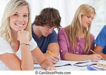 A close up shot of a smiling girl with her study friends as she looks into the camera