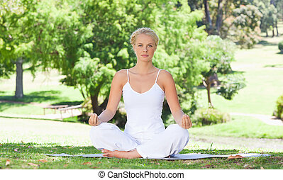 Woman sitting on the meadow doing yoga exercises