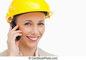 Portrait of a woman wearing safety helmet on the phone