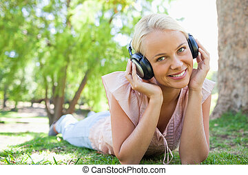 Smiling woman listening to music while lying on the lawn
