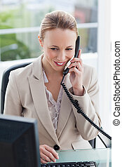 Woman in a suit on the phone in her office