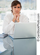 Serious young businessman with a laptop