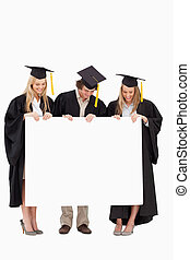Three smiling students in graduate robe holding a blank sign...