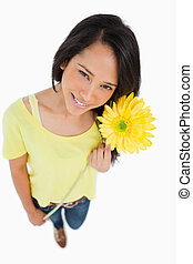High-angle view of a Latino woman holding a flower against...