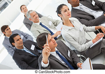 Man asks question at business meeting - A man is asking a...