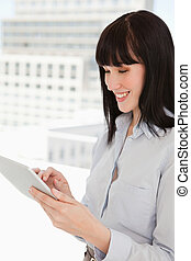 A happy woman using her tablet pc in her office - A smiling...