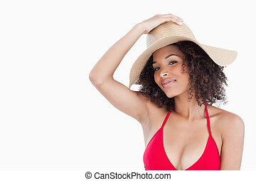Beautiful woman wearing a swimsuit while holding her hat