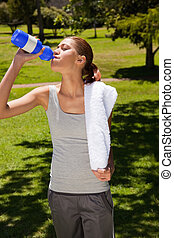 Woman drinking from a sports bottle