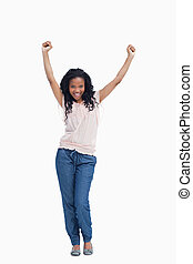 A young happy woman stands with her hands in the air - A...