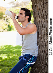 Man drinking from a sports bottle while resting