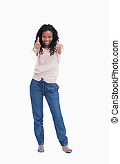A young woman standing with her thumbs up - A young smiling...