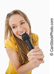 Fisheye view of blonde girl singing with a microphone...
