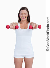 Red dumbbells being held by a young woman