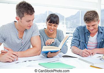 A group of students sitting together as they all study