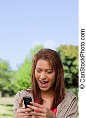 Woman with a happy expression reading a text message - Woman...