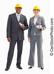 Businesspeople wearing hard hats - Two businesspeople are...