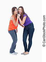 Two teenagers bending over while singing - Two smiling...
