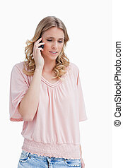 Young blonde woman is talking on her mobile phone