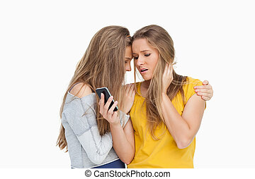 Upset young woman looking her cellphone consoled by her friend
