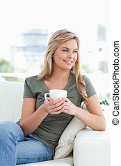 Woman with cup in hands, smiling and looking to the side
